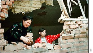 woman behind broken wall in Chechnya